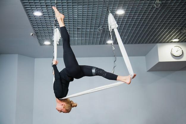 Красивая фитнес-модель на летающем гамаке для йоги