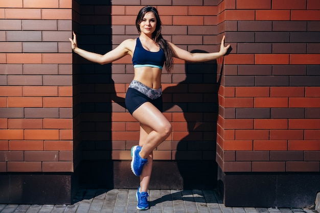 Beautiful fitness model posing against a brick wall.