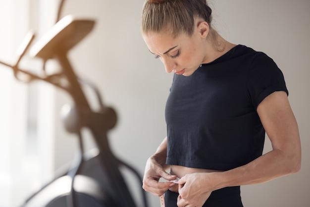 슬림 한 몸매를 가진 아름다운 피트니스 모델은 피트니스 클럽에서 허리를 측정하고 건강한 영양과 체중 감량 개념을 측정합니다.