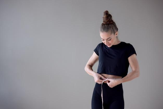 Красивая фитнес-модель с тонким телом измеряет талию в фитнес-клубе, концепции здорового питания и похудения.