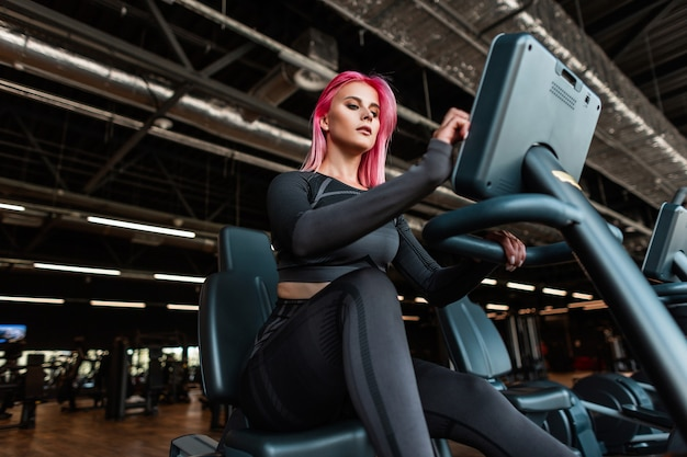 黒のスタイリッシュなスポーツウェアの美しいフィットネスモデルの女性がエアロバイクでトレーニングを開始します
