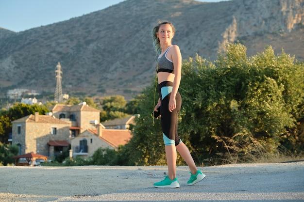 Beautiful fitness runner girl using smartphone and headphones listening music