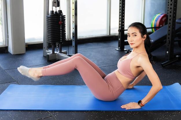 Красивая фитнес-стройная женщина в спортивной одежде упражнение в тренажерном зале, стройное тело азиатской сексуальной девушки - образ жизни здоровая женщина фитнес-концепция Premium Фотографии