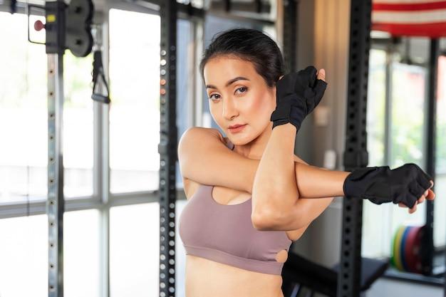 Красивая фитнес стройная женщина в спортивной одежде, протягивая руку в тренажерном зале, стройное тело азиатской сексуальной девушки - образ жизни здоровая женщина фитнес-концепция