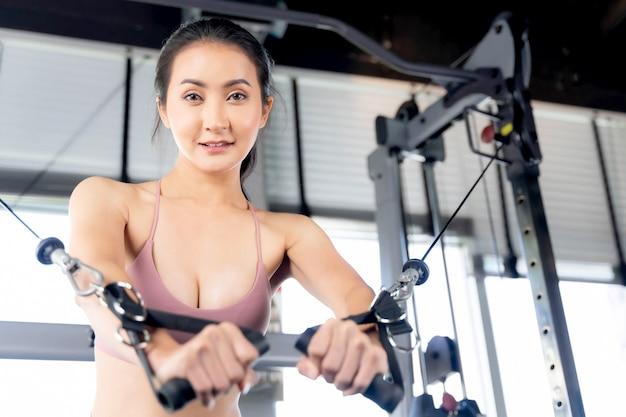 Красивая стройная фитнес-женщина в спортивной одежде, работая с кабельным кроссовером в тренажерном зале, стройное тело азиатской сексуальной девушки - концепция фитнес-модели.
