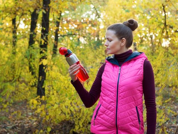 가 숲에서 손에 스포츠 물병 또는 등장 음료와 운동복에 아름 다운 피트 니스 스포츠 소녀.