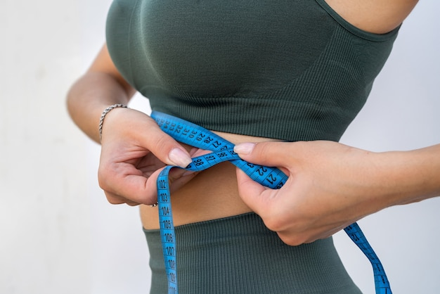 Beautiful fitness sports young woman measuring her body with measure tape over on grey background. healthy lifestyle