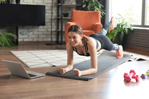 ノートパソコンでオンラインチュートリアルを見たり、リビングルームでトレーニングしたりする板のエクササイズをしている美しいフィットネス女性。健康的な生活様式。女の子は家でスポーツに行きます。