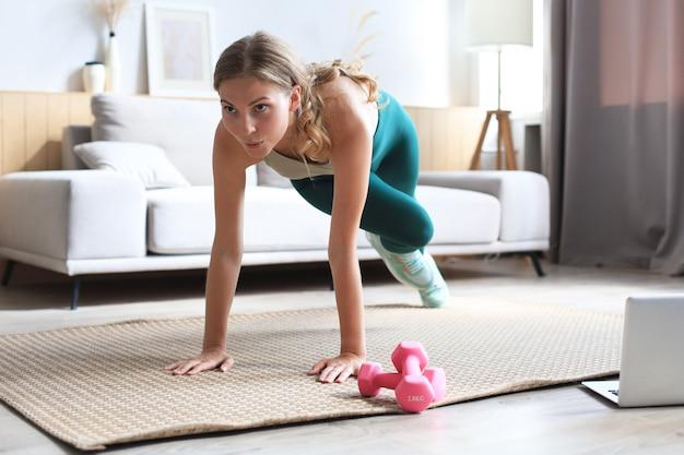 ノートパソコンでオンラインチュートリアルを見たり、リビングルームでトレーニングしたりする登山家のエクササイズをしている美しいフィットネス女性。健康的な生活様式。女の子は家でスポーツに行きます。