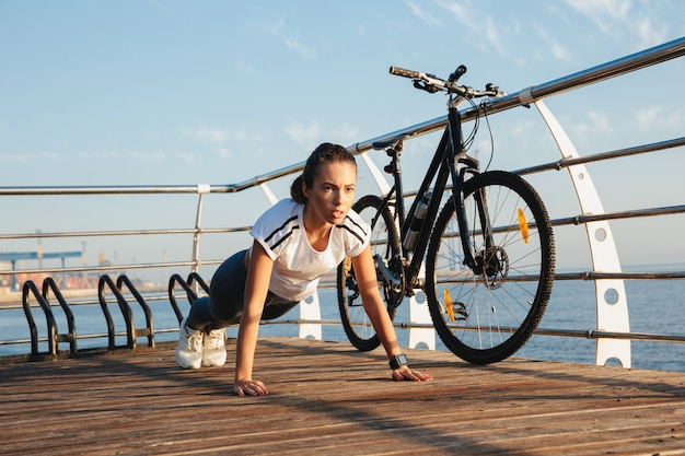 Beautiful fitness woman doing plank exercise at the beach, riding on a bicycle