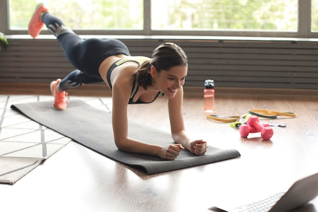 Beautiful fitness woman doing a plank exercise watching online tutorials on laptop, training in living room. healthy lifestyle. girl goes in for sports at home.