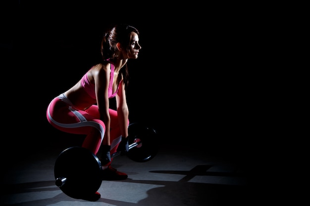 Beautiful fitness woman doing squats with a barbell