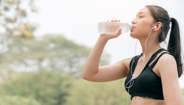 Beautiful fitness woman drinking water after work out exercising.