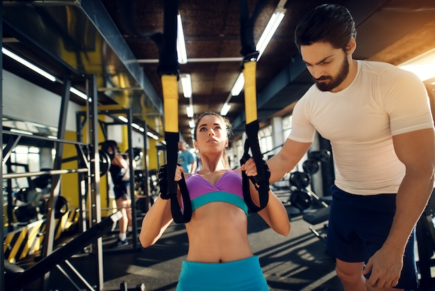 Beautiful fitness woman exercising with trx system in the gym with a muscular personal trainer.