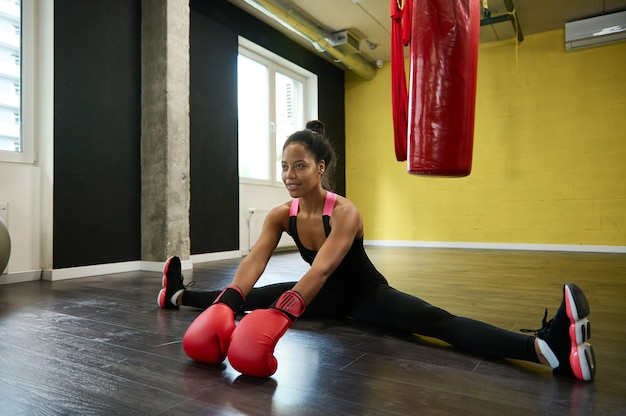 Beautiful fitness woman, female boxer wearing red boxing gloves and sitting on twine in the floor of a sports gym with a punching bag. martial combat art and stretching concept, sport, wellness