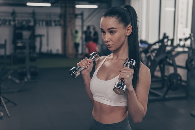 Beautiful fitness woman looking concentrated, exercising with dumbbells, copy space