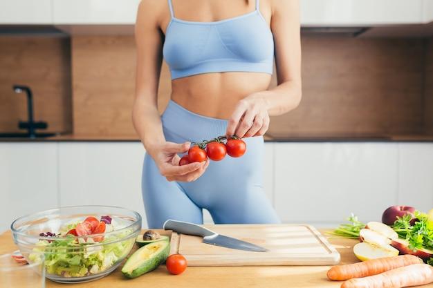 Красивая женщина фитнеса, готовит здоровую пищу дома