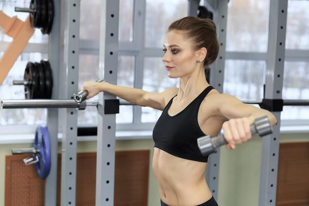 아령을 들고 아름 다운 피트 니스 여자입니다. 가벼운 무게를 드는 스포티 한 여자. 근육을 구축 운동 맞는 소녀. 피트니스 및 보디 빌딩.