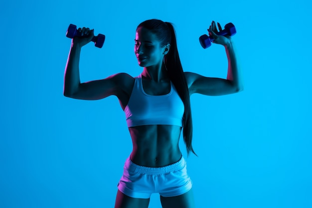 Beautiful fitness woman working out with dumbbells over blue light background