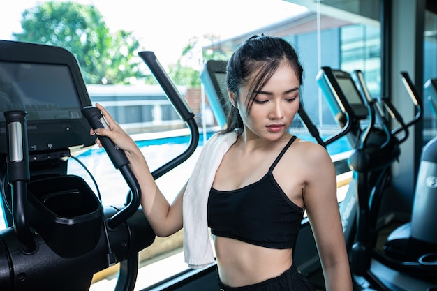Beautiful fitness women prepare for running at the treadmill in the gym.