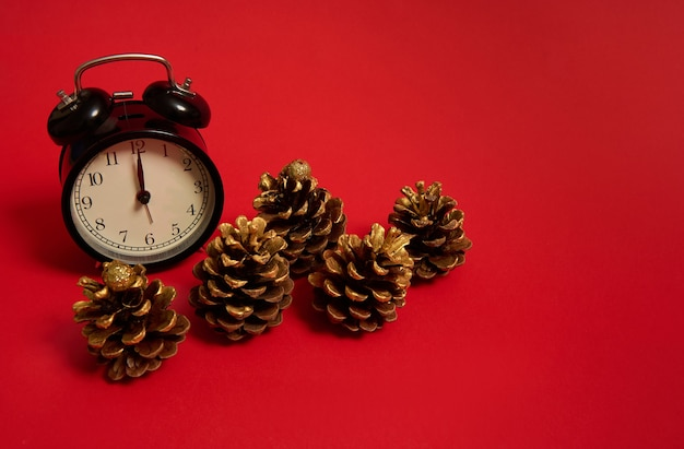 Beautiful five pine cones decorated with gold paints and a black alarm clock with midnight on the dial, isolated on a colored red background with copy space for ad. it's midnight, christmas concept
