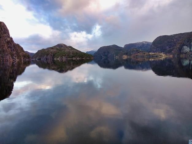 曇り空の下の崖や町を反映した、ノルウェーのベルゲン近郊の美しいフィヨルド