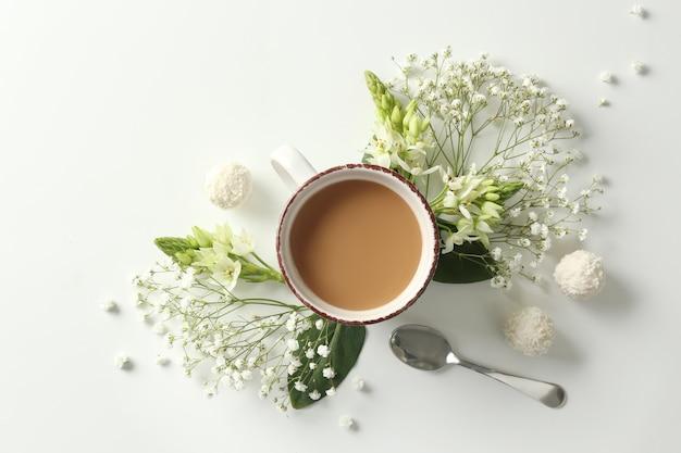 白いスペースにコーヒーと花のカップと美しいフラットレイ構成