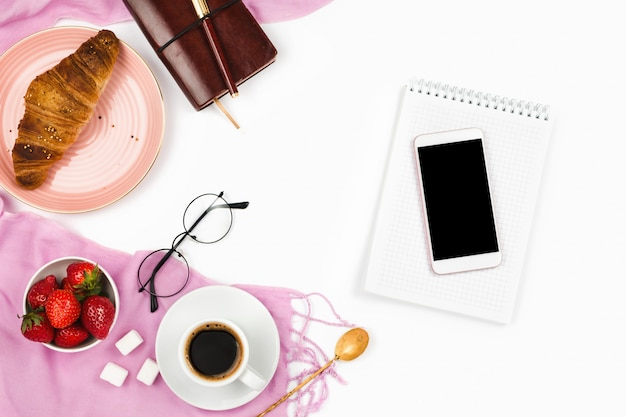Beautiful flatlay arrangement with croissant, cup of coffee, fresh strawberries, smartphone with black copyspace and other business accessories: concept of busy morning breakfast, white background.