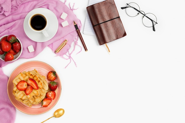 Beautiful flatlay arrangement with cup of coffee, hot waffles with cream and strawberries, glasses and other business accessories: concept of busy morning breakfast, white background.