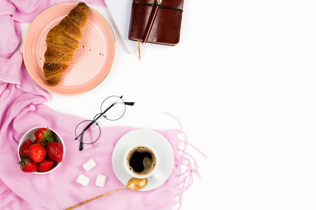 Beautiful flatlay arrangement with wholewheat croissant, cup of espresso coffee, fresh strawberries and business accessories: concept of busy morning breakfast, white background. copyspace