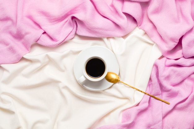 Beautiful flatlay  a cup of morning black coffee and golden spoon in bed. top view