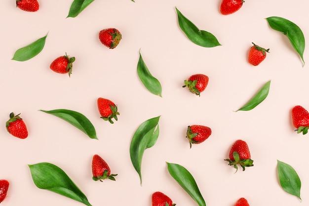 Красивая плоская картина листьев рускуса и свежей органической клубники на пастельном фоне