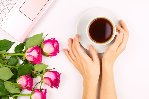 Beautiful flatlay with a cup tea in a woman's hand, laptop and roses, concept of good morning or woman's workspace.