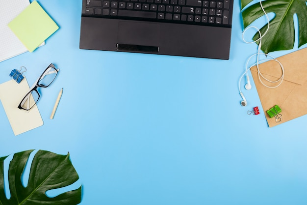 Beautiful flatlay with a laptop, glasses, philodendron leaves and other business accessories. concept of a home office. flat lay.