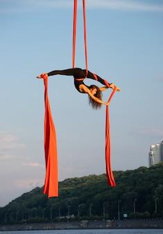 Красивая гибкая художница с воздушным шелком на фоне неба и реки
