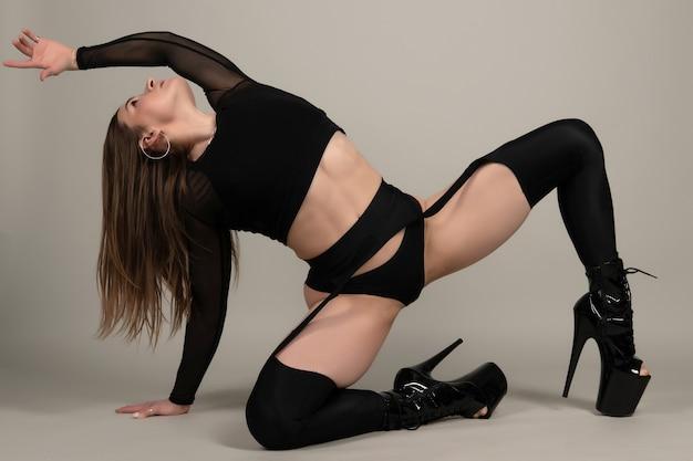 Красивая гибкая девушка полюс танцор на высоких каблуках позирует