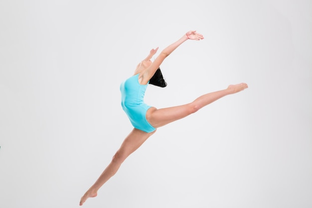 Beautiful flexible woman gymnast isolated on a white wall