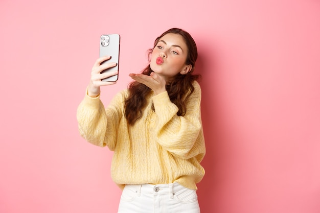 Beautiful flirty girl taking selfie on smartphone, sending air kiss during video chat, standing against pink wall. copy space
