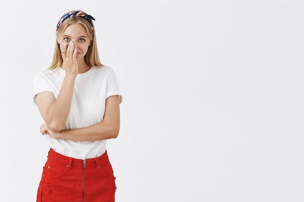 Красивая кокетливая молодая блондинка позирует у белой стены
