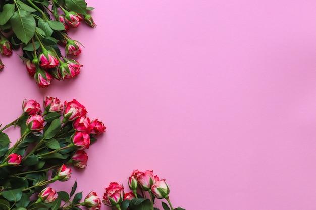 ピンクの背景に美しいフラワーアレンジメント。ピンクのバラとテキストのコピースペース