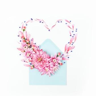Красивые цветочные композиции. розовые хризантемы в форме сердца с конвертом на белом фоне. плоская планировка, вид сверху.