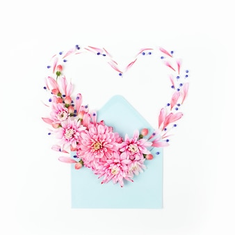 Beautiful floral arrangements. pink chrysanthemums in the shape of heart with envelope on white background. flat lay, top view.