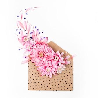 Красивые цветочные композиции. розовые хризантемы с конвертом на белом фоне. плоская планировка, вид сверху.