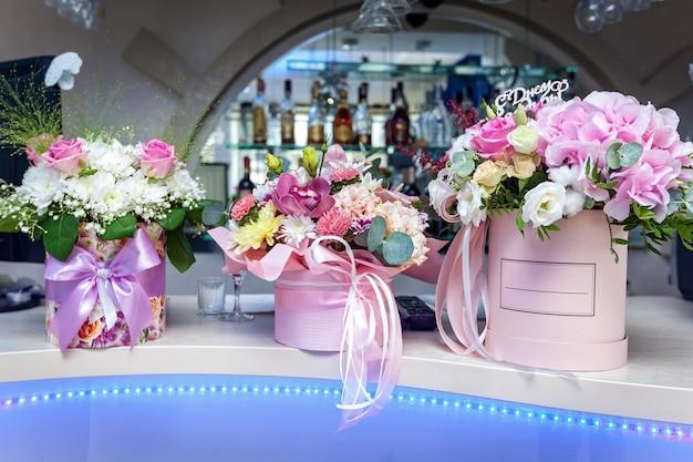 분홍색 리본으로 장식된 고급 상자에 장미와 함께 아름다운 꽃꽂이가 바에 놓여 있습니다.