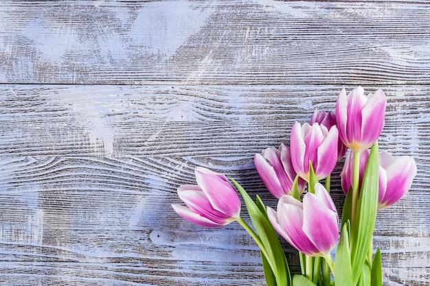 木の板に新鮮なチューリップの花と美しい花の背景