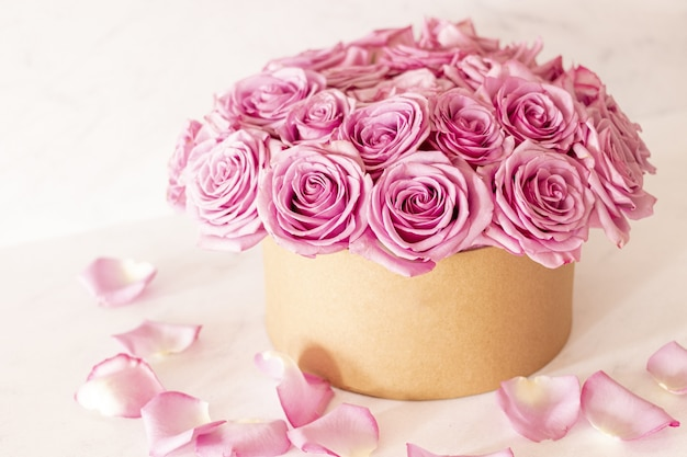 Beautiful floral bouquet with pink roses in a box on a pink background