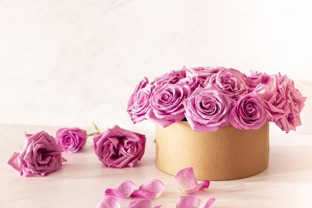 Красивый цветочный букет с розовыми розами в коробке на розовом фоне