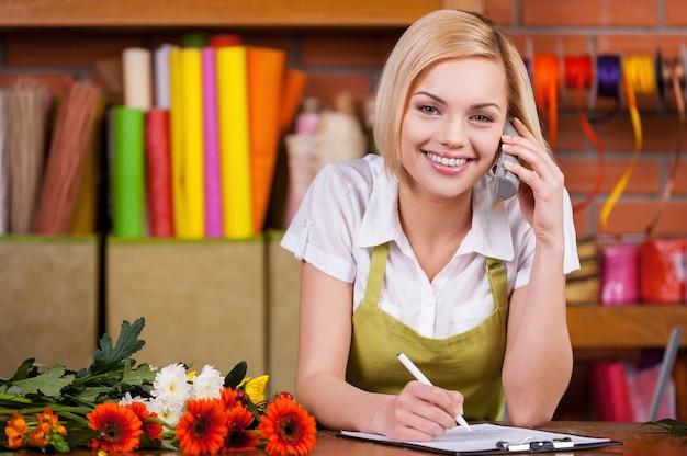 Красивый флорист за работой. красивая молодая женщина-флорист пишет что-то в блокноте и разговаривает по телефону, стоя на своем рабочем месте