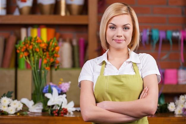 Красивый флорист на рабочем месте. красивая молодая женщина-флорист держит скрещенными руками и смотрит в камеру, стоя возле своего рабочего места