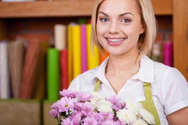Красивый флорист. красивая молодая женщина со светлыми волосами в фартуке, держа букет цветов и улыбаясь